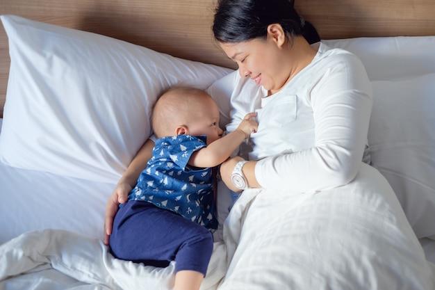 Mãe asiática está amamentando asiática pouco bonitinha 14 meses Foto Premium