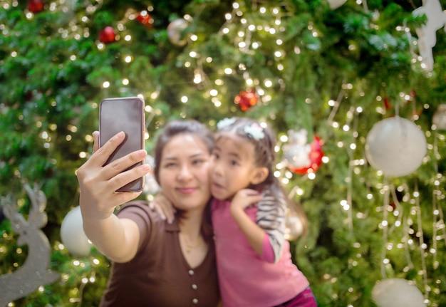 Mãe asiática mão segure móvel com a filha para tirar foto de selfie Foto Premium