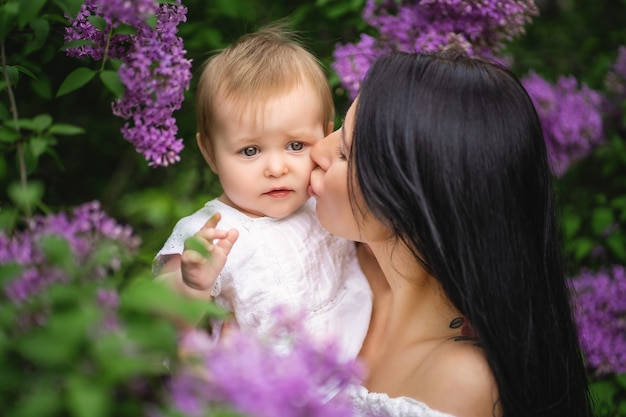 Mãe beija a filha perto de um lilás florescendo. cor púrpura. imagem de primavera Foto Premium