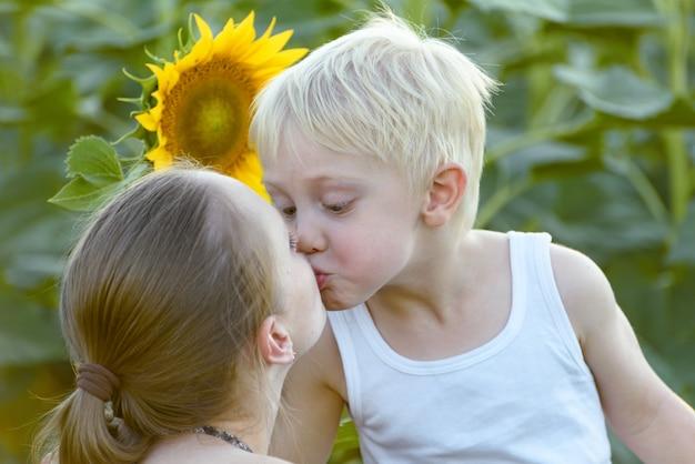 Mãe beija seu filho pequeno, girassóis florescendo Foto Premium