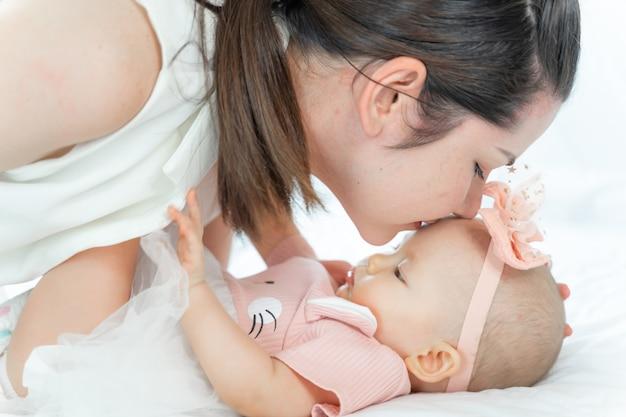 Mãe beijando a cabeça de seu bebê dormindo Foto gratuita