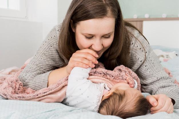 Mãe beijando a mão do bebê dormindo Foto gratuita