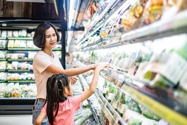 Mãe bonita asiática nova que guarda a cesta do mantimento com sua criança que anda no supermercado. Foto Premium