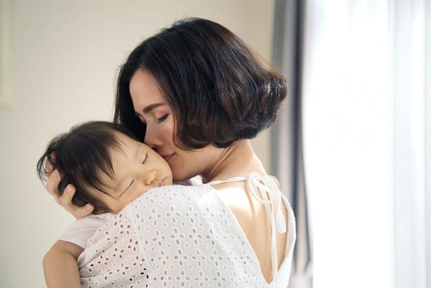 Mãe bonita asiática que abraça o bebê de sono em seus braços e que beija a criança delicadamente. a mãe fecha os olhos enquanto segura a cabeça do bebê para descansar no ombro. toque de amor e relacionamento familiar. Foto Premium
