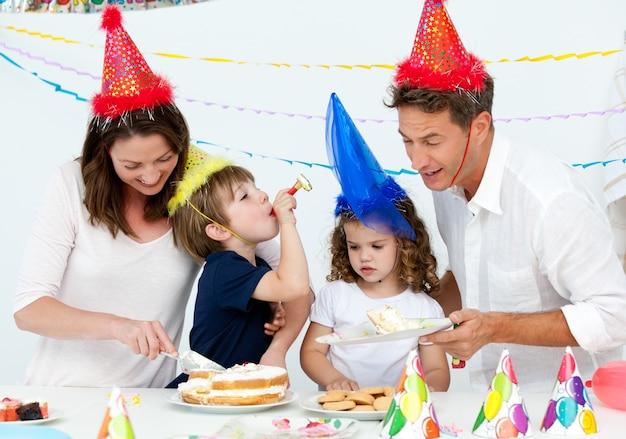 Mãe bonita que serve um bolo de aniversário para sua família Foto Premium