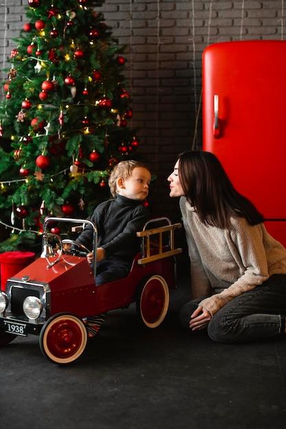 Mãe brincando com o bebê ao lado da árvore de natal Foto Premium