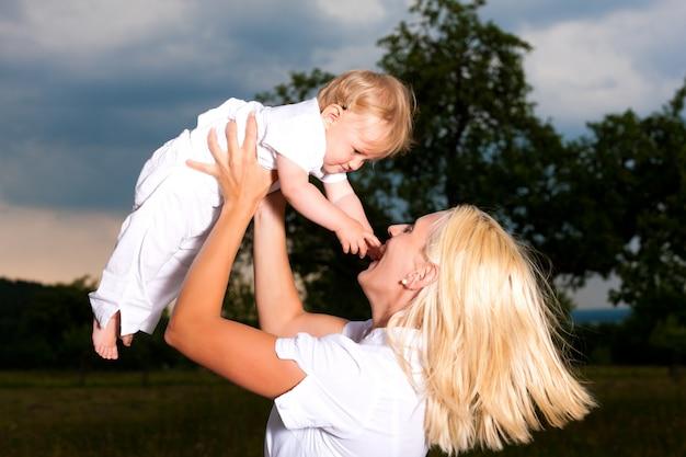 Mãe brincando com seu bebê ao ar livre Foto Premium