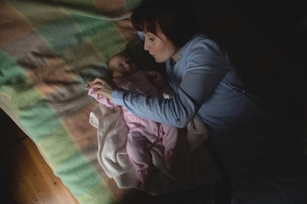Mãe brincando com seu bebê no quarto Foto gratuita