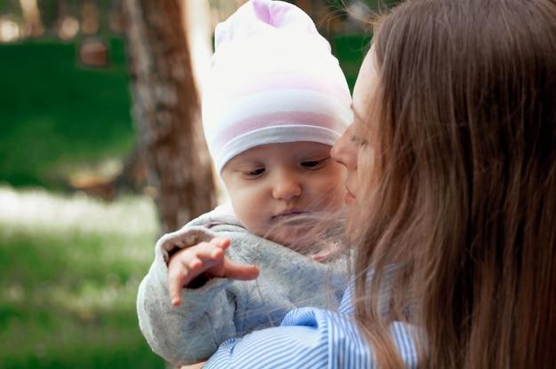 Mãe caminha com o bebê no parque. o bebê em seus braços. primavera. Foto Premium