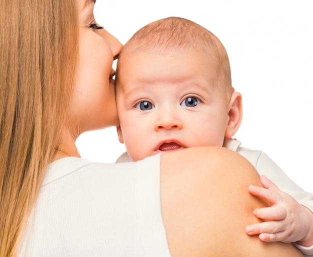Mãe carinhosa beija o bebê e abraça. Foto Premium
