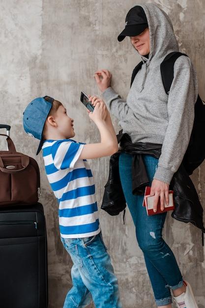Mãe carrega um filho pequeno em uma mala na sala de espera de transporte. Foto Premium
