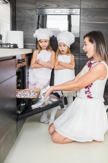 Mãe chocada e filha olhando para biscoitos na cozinha Foto gratuita