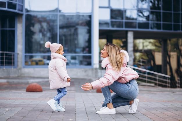 Mãe com a filha pequena, vestida com um pano quente fora da rua Foto gratuita