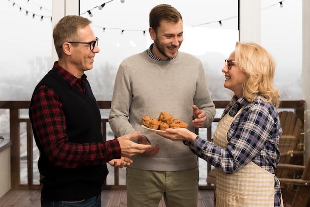 Mãe com avental dando muffins para filho e pai Foto gratuita