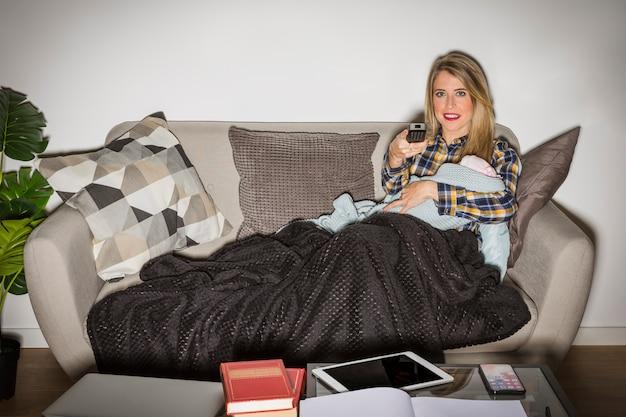Mãe, com, bebê, olhando televisão Foto gratuita