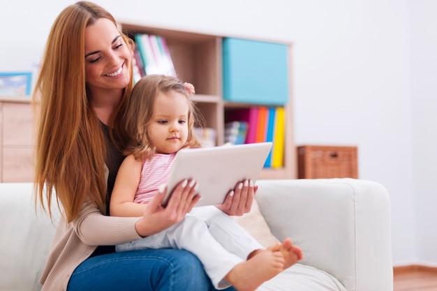 Mãe com bebê usando tablet digital em casa Foto gratuita