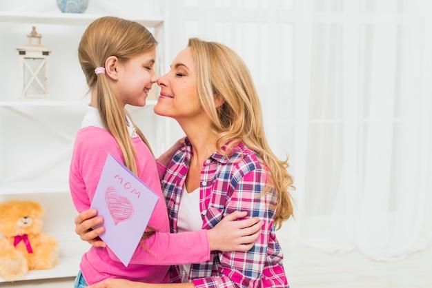 Mãe, com, cartão, tocar, narizes, com, filha Foto gratuita
