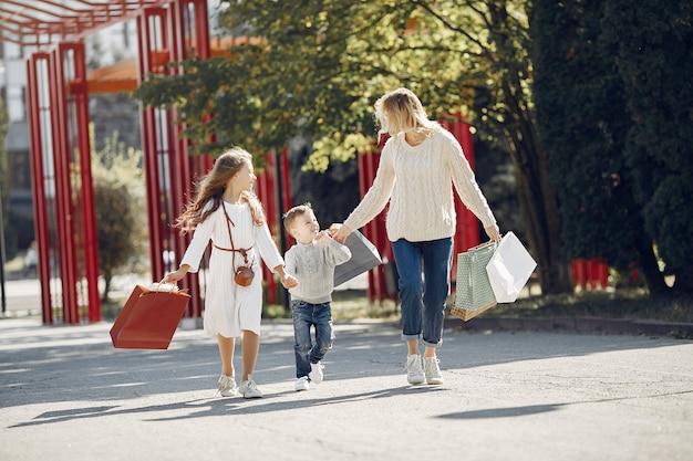 Mãe com criança com sacola de compras em uma cidade Foto gratuita