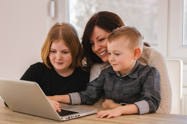 Mãe com crianças assistindo desenhos no computador em casa Foto Premium