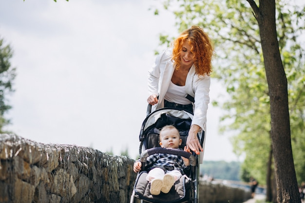 Mãe, com, dela, filho pequeno, em, um, carruagem bebê, parque Foto gratuita