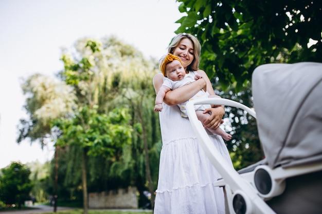 Mãe com filha bebê andando no parque Foto gratuita