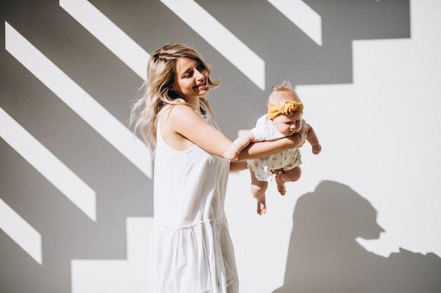 Mãe com filha bebê no fundo branco Foto gratuita