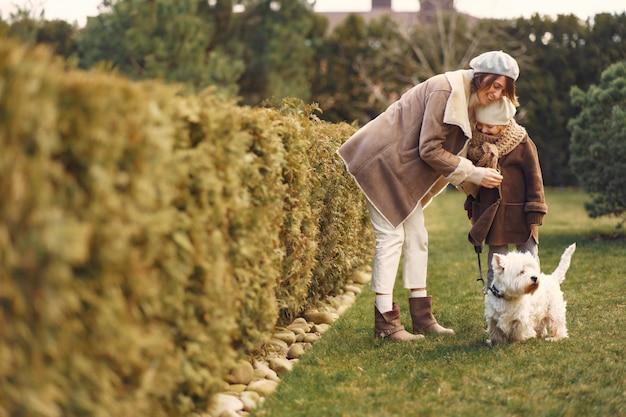 Mãe com filha caminha com um cachorro Foto gratuita