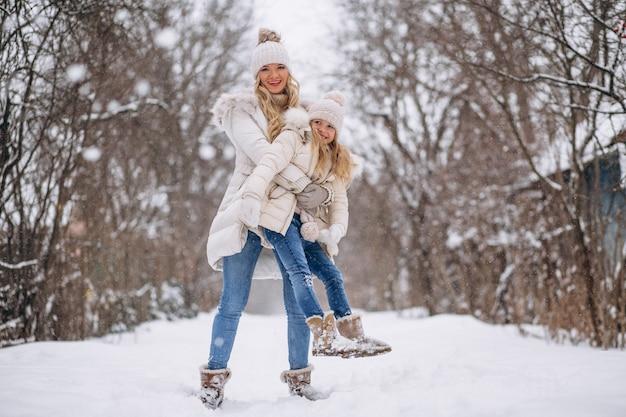 Mãe com filha caminhando juntos em um parque de inverno Foto gratuita
