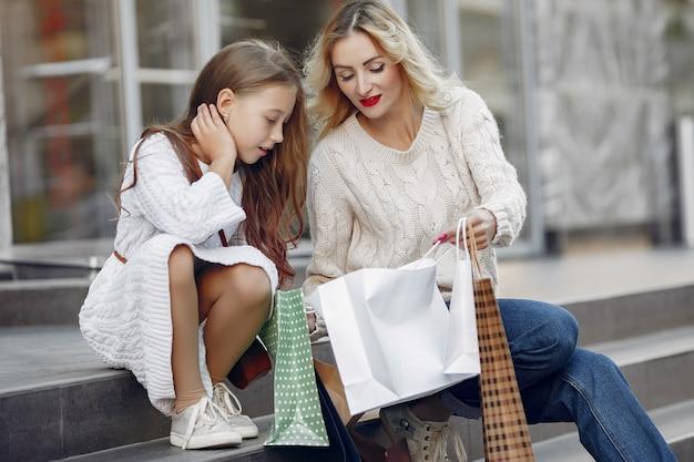 Mãe com filha com sacola de compras em uma cidade Foto gratuita