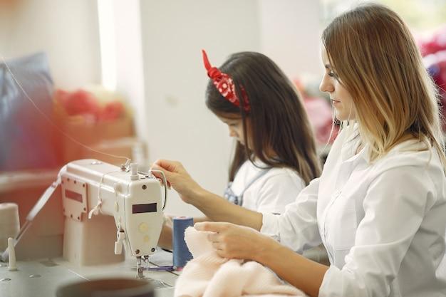 Mãe com filha costurar roupas na fábrica Foto gratuita
