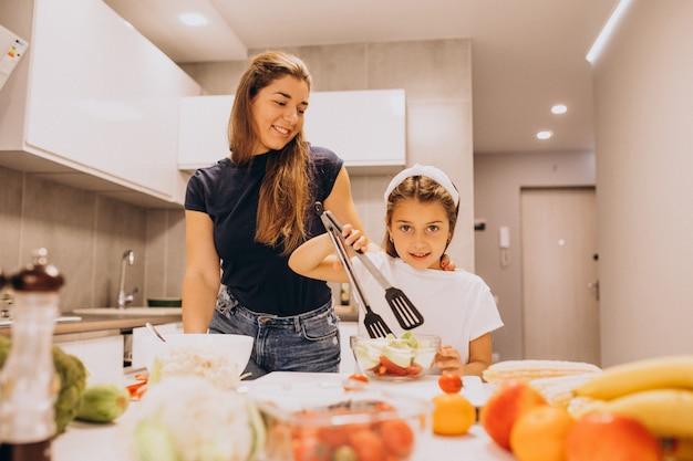 Mãe com filha cozinhar juntos na cozinha Foto gratuita