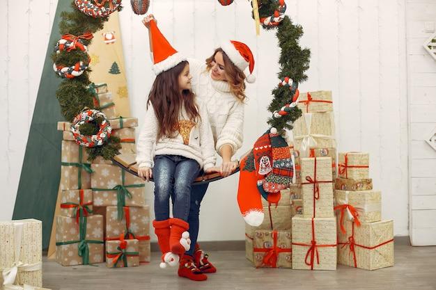 Mãe com filha em uma decoração de natal Foto gratuita