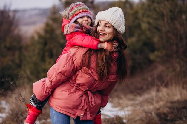 Mãe com filha em uma floresta de inverno Foto gratuita