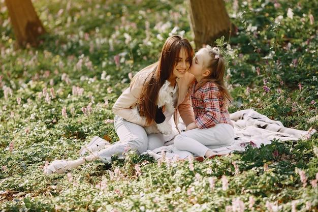 Mãe com filha em uma floresta de primavera com cachorro Foto gratuita
