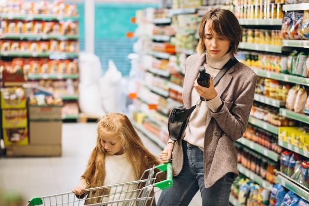 Mãe com filha em uma mercearia Foto gratuita