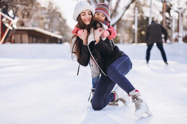 Mãe com filha ensinando patinação no gelo em uma pista Foto gratuita