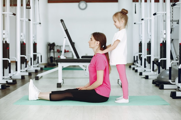Mãe com filha estão engajados em ginástica no ginásio Foto gratuita
