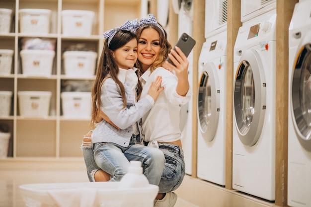 Mãe com filha lavando roupa na lavanderia self-service Foto gratuita