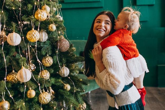 Mãe com filha pela árvore de natal Foto gratuita