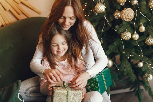 Mãe com filha perto de árvore de natal Foto gratuita
