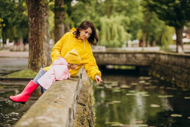 Mãe com filha se divertindo no parque em um tempo chuvoso Foto gratuita
