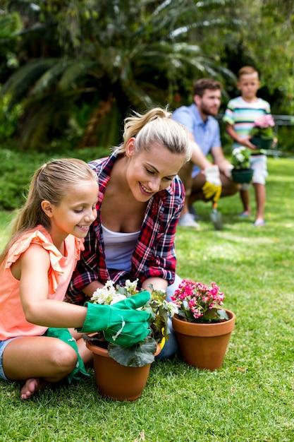 Mãe com filha segurando vasos de flores no quintal Foto Premium