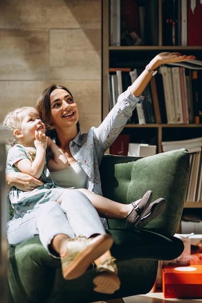Mãe com filha sentada em um sofá em casa Foto gratuita