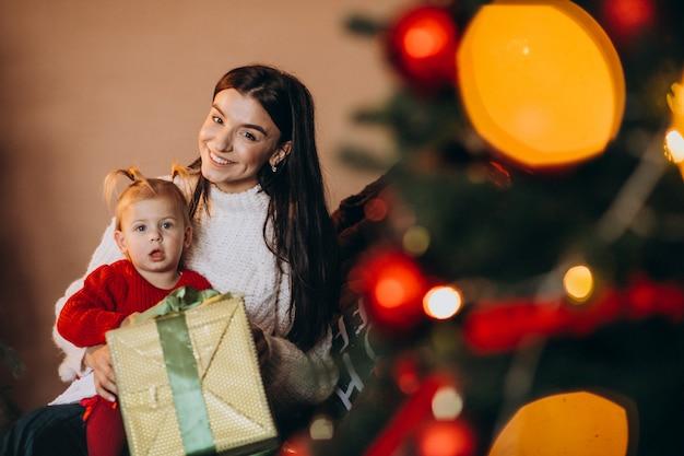 Mãe com filha sentada perto da árvore de natal Foto gratuita