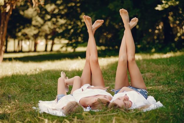 Mãe com filhas em um parque Foto gratuita