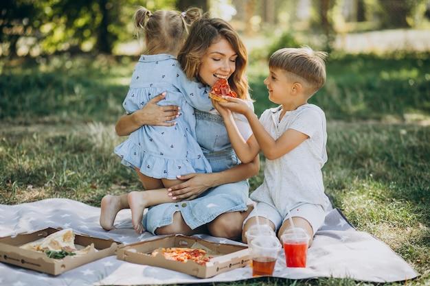 Mãe com filho e filha comendo pizza no parque Foto gratuita