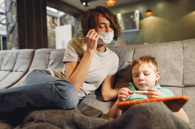Mãe com filho menor sentado em casa em quarentena Foto gratuita