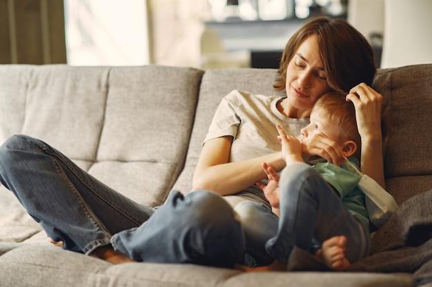 Mãe sentada em sofá com filho pequeno