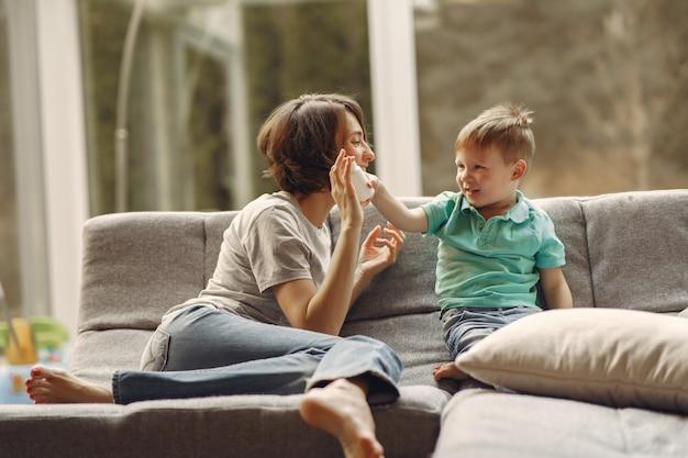 Mãe com filho menor sentado em casa em quarentena | Foto Grátis
