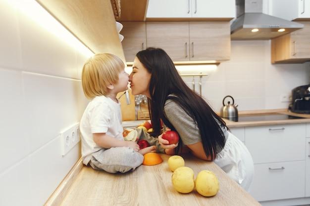Mãe com filho pequeno a comer frutas na cozinha Foto gratuita